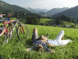 Summer vacation in Bavaria - mountain biker on a mountain meadow